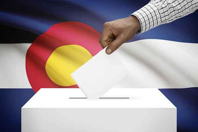 PROMO Politics - Election Ballot Box Hand Colorado Flag Vote - iStock - Niyazz