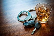 Crime - Drink Drive Whiskey Alcohol Key Fob Handcuff Table Glass - iStock - AlexRaths